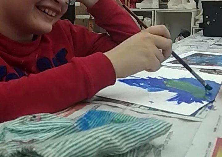 Sebastián pintando sonriente y feliz